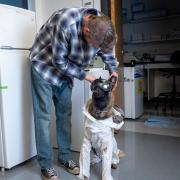 Student with service dog in a lab coat and goggles