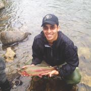 Engineering and jazz music student shows off trout caught while fly fishing