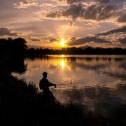 Person fishing on a lake at sunset