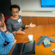 Colleagues attend a webinar in a conference room