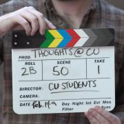 Someone holds a CU Boulder film production slate board