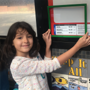 A Whittier Elementary School student uses a green frame to show that she likes the sign being low enough for children to read it. Students used green and red frames to frame the things they liked and didn't like about the HOP.