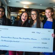 Business minor business plan competition winners pose with giant check