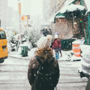 Person walking around city while snowing