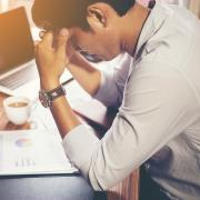 Stressed-out man sits at desk with face in hands