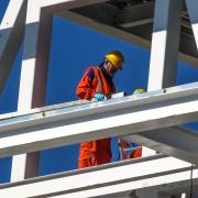 A construction worker in a helmet is seen surrounded by steel framing.