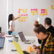 person places sticky notes on wall in a conference room