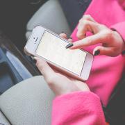 Woman in pink coat checks calendar on iPhone