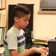 Child plays piano during lesson