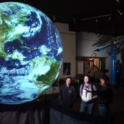 Community members look at huge, glowing model of Earth