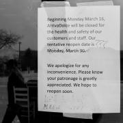 Sign announces business closing due to COVID-19 with tentative reopening date of March 30, later scratched out with pen and question marks.