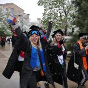 Graduates walk in commencement procession, some donning ski goggles in the snow