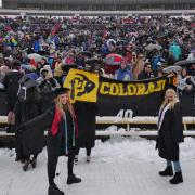 Graduates hold up a black and gold Colorado banner