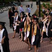 Graduates enjoy the procession from the quad to CU Boulder's 2018 main commencement ceremony at Folsom Field. Photo by Glenn Asakawa.