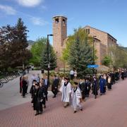 Dignitaries and faculty process from Norlin Quad to the main commencement ceremony. Photo by Glenn Asakawa.