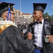Two graduates shake hands on Folsom Field before the commencement ceremony. Photo by Glenn Asakawa.