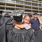 Trevor Jordan, sociology major and minor in anthropology, hugs his daughter Violet, 6, before the ceremony. Photo by Glenn Asakawa.