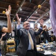 Chancellor DiStefano raises hands at football kickoff luncheon