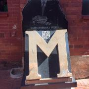 Gold letter M plaque with cutout of Nelson Mandela