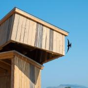 Swallow flies into the nest sculpture opening.