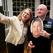 Kristen Browning-Blas takes a selfie with Scott Kelly while holding a cutout of NASA astronaut Kjell Lindgren