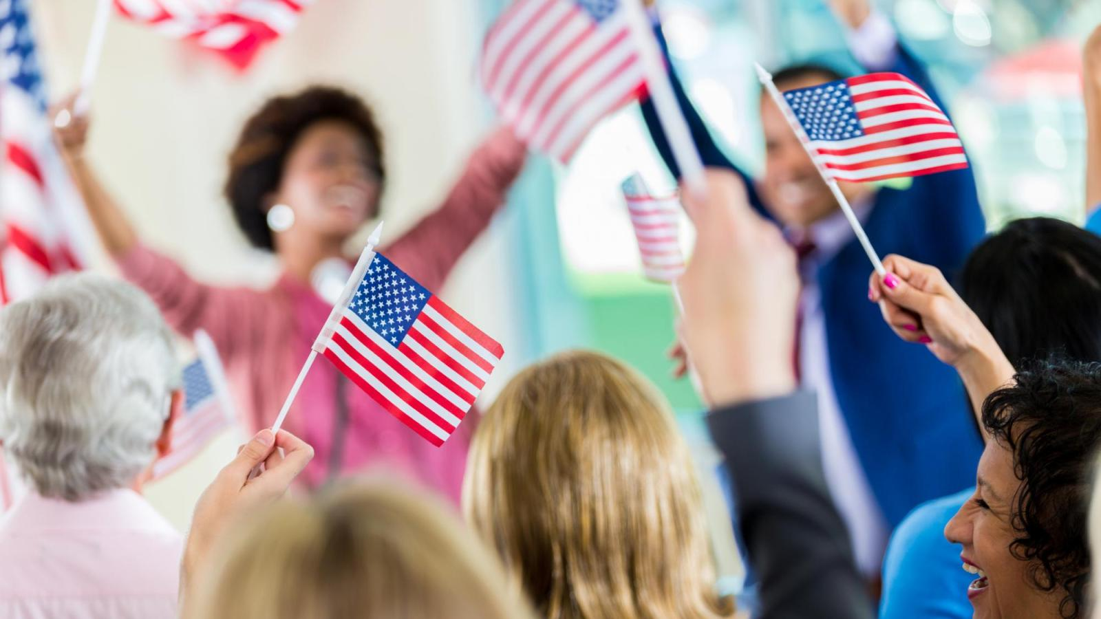 Women wave American flags at an election event