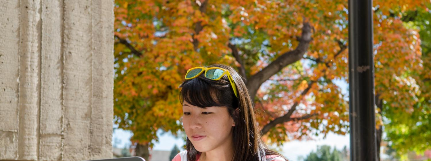 Asian female student working at a laptop while on campus