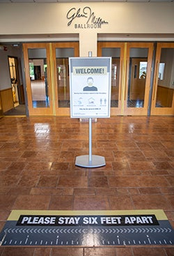 Entrance to the UMC with signs indicating that visitors must wear a face covering and stay six feet apart