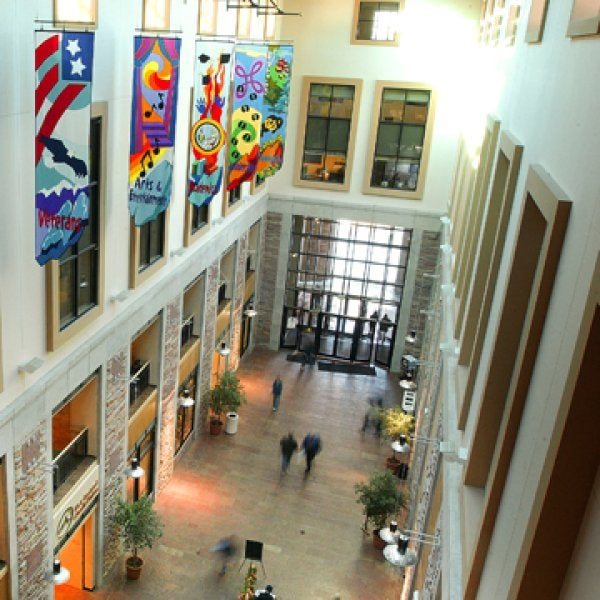 The inside of the UMC large Atrium is shown . It is 5 stories high, all enclosed, with colorful banners hanging down on one side from the ceiling. The banners represent the various areas of the UMC: Veterans, Diversity, Events, Programs, Arts and Culture.