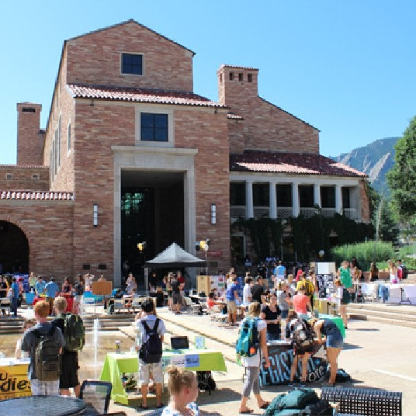 A photo showing the UMC north patio area with students sitting at the outside tables and mingling at the Student Involvement Fair.