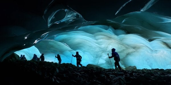 A photo of hikers at night in front of a cave of ice