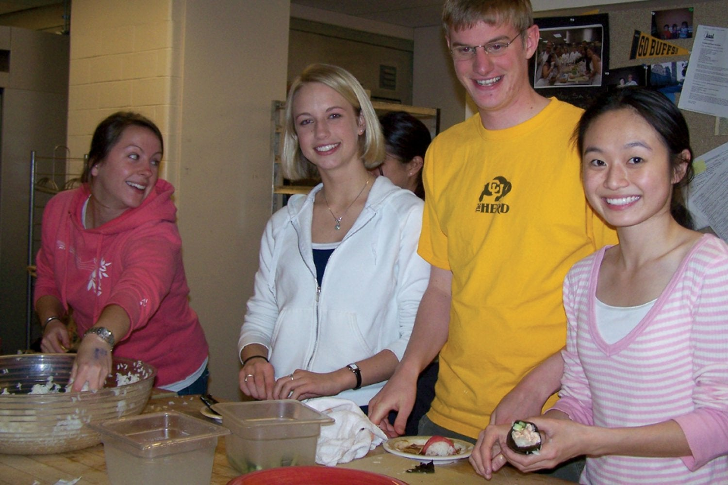 Students taking a cooking class where they learn to make sushi.