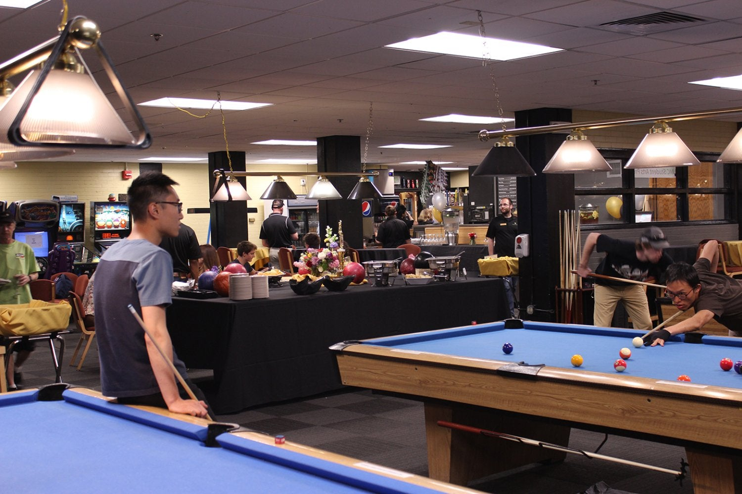 Students play billiards during a special event at The Connection