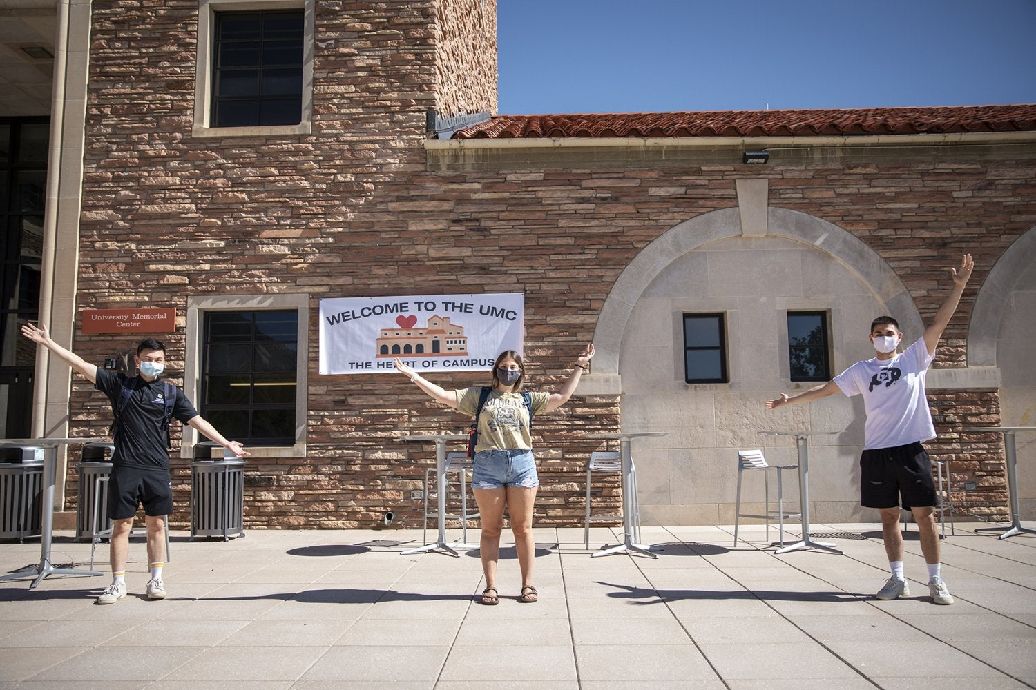 Three students stand outside the UMC
