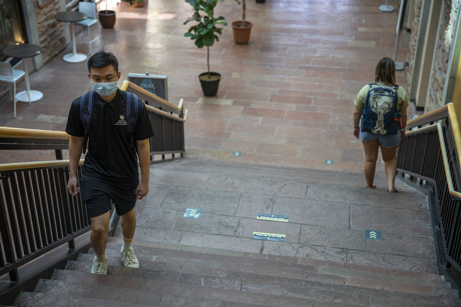 Two students walk up and down the main atrium stairs in the UMC