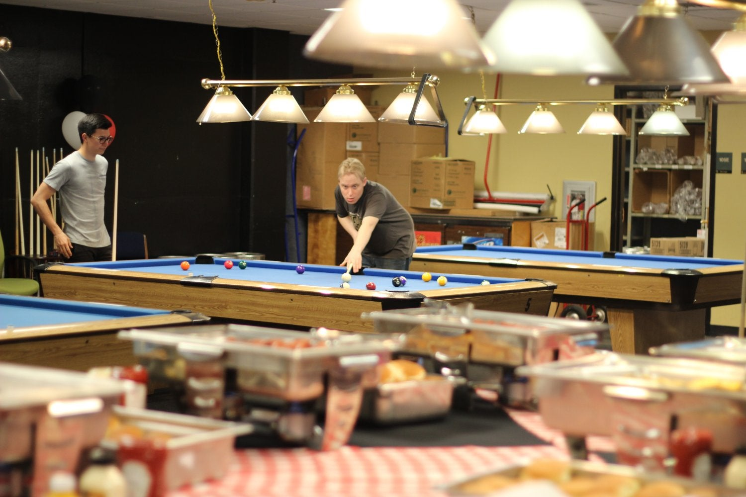 Students play pool/billiards at First Friday Buff Club
