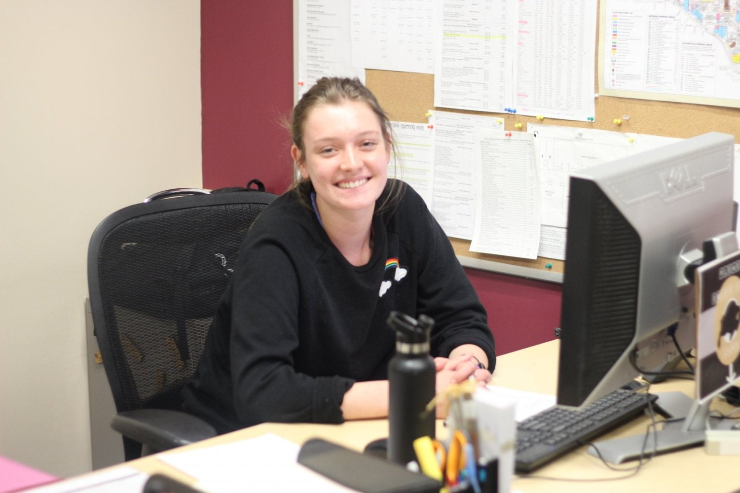 A student at her desk in the CU Events Planning & Catering office