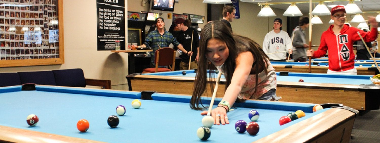 A photo of students playing billiards at The Connection Bowling, Billiards & Games room on the first floor of the UMC. This photo was taken during Midnight Breakfast 2014.