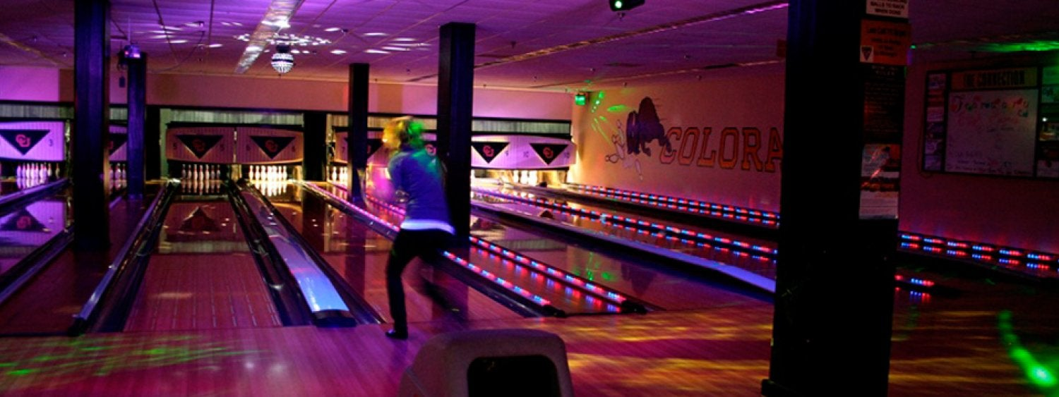 A student bowler with colored lights in the lanes.