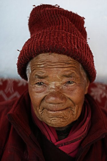 A photo of an elderly Indian woman wearing a red knitted hat