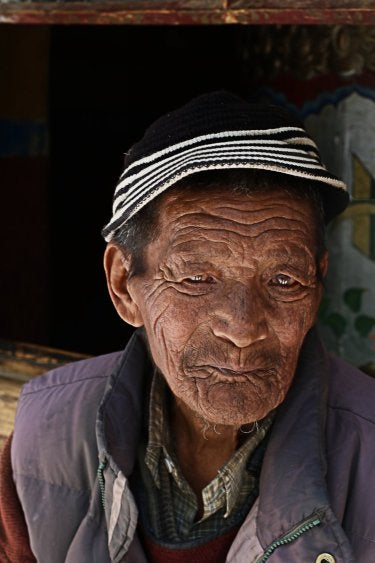 A photo of an elderly Indian man wearing a black knitted hat