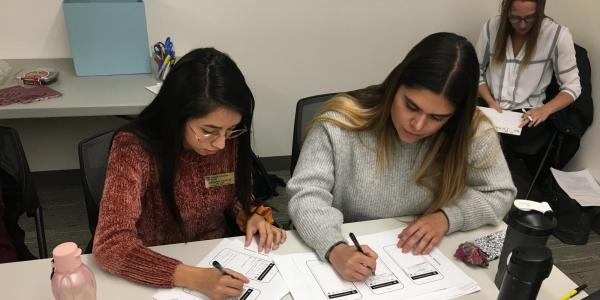 Two students sketching designs