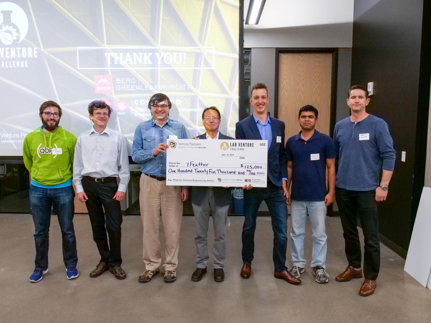 ifeather team posing with check award