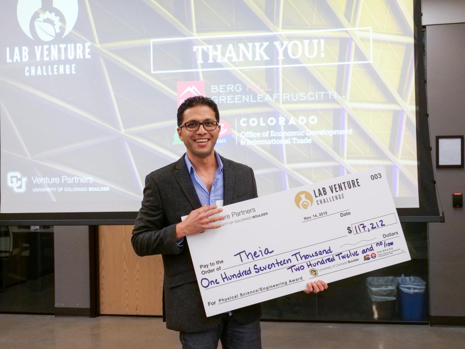 alireza vahid posing with check award