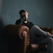 man sitting on leather chair holding head in hands