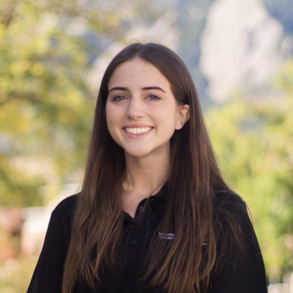 Grace Caruso posing for a headshot wearing a VRC polo standing in front of the Flatirons