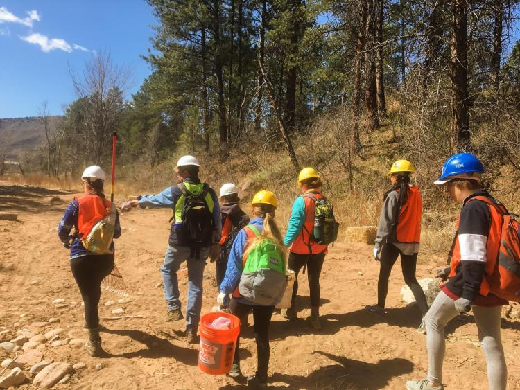 Students in bright vests working in the mountains