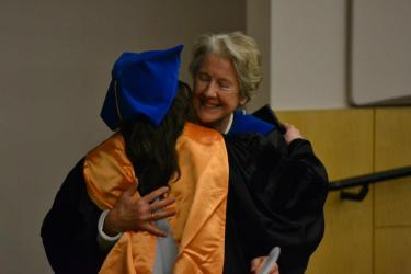 Dr. Annaleigh Curtis receiving her doctoral hood from Dr. Jaggar at graduation