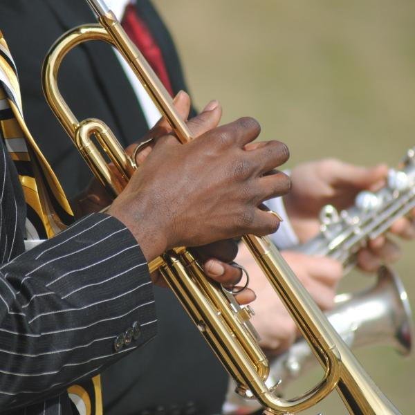 A man's hands playing the trumpet.